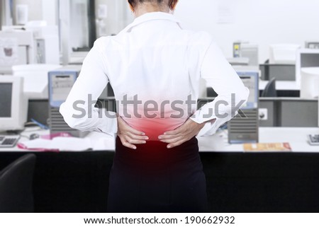Young businesswoman having back pain while working at office  - stock photo