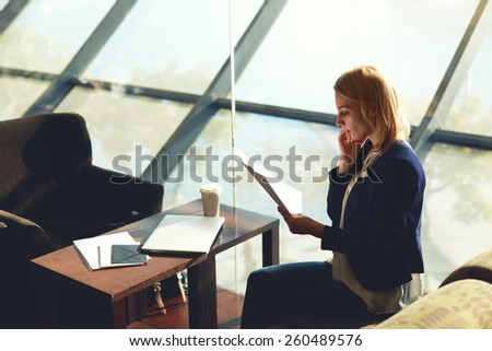 Young businesswoman having cell phone conversation while examining paperwork in luxury coffee shop, filtered image, soft focus - stock photo