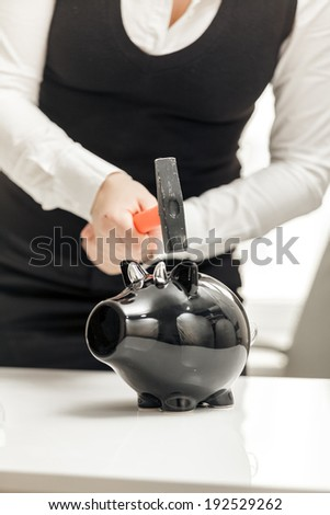 Young businesswoman hitting piggy bank with hammer - stock photo