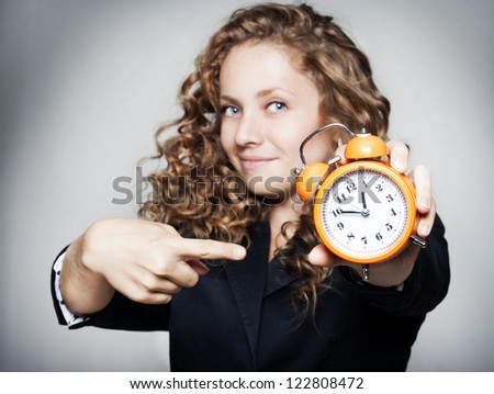 Young businesswoman holding a clock - stock photo
