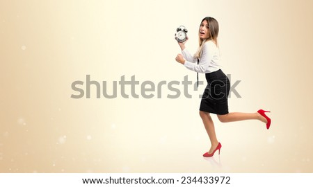 Young businesswoman holding an antique clock over ocher background  - stock photo