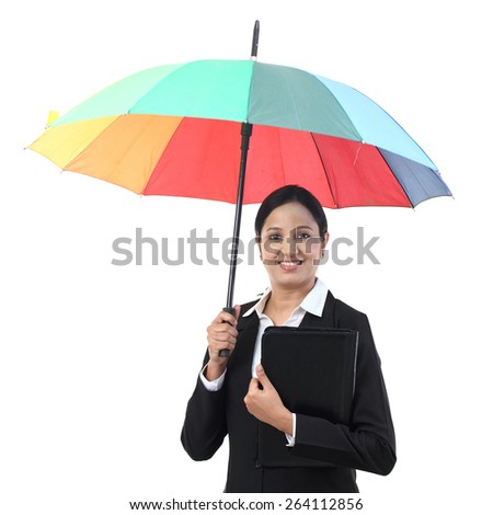Young businesswoman holding an umbrella - stock photo