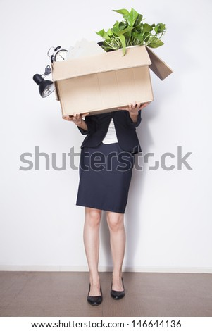 Young Businesswoman holding box of office items - stock photo