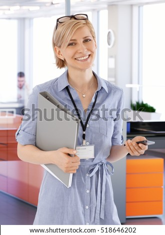 Young businesswoman holding folder and mobile, smiling happy.