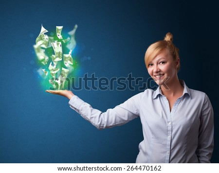 Young businesswoman holding glowing paper moneys in her hand - stock photo