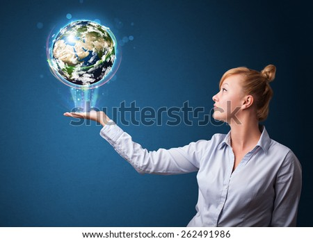 Young businesswoman holding in her hand a glowing earth globe, Elements of this image furnished by NASA - stock photo