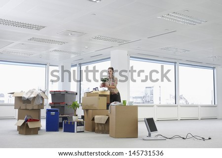 Young businesswoman holding potted plant near cartons and equipment in empty office space - stock photo