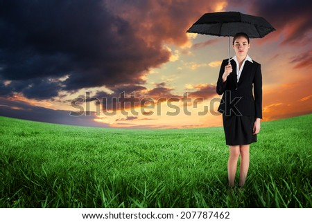Young businesswoman holding umbrella against green field under orange sky