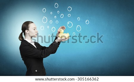 Young businesswoman holding yellow rubber duck toy in palm