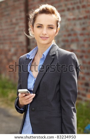 young businesswoman holds her mobile, outdoor shoot with blurred red brick wall as background, can be used as copy space - stock photo