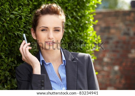 young businesswoman holds her mobile, outdoor shoot with blurred red wall as part of background, can be used as copy space - stock photo