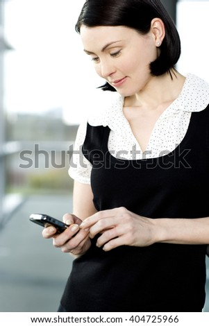 Young businesswoman in an office using a mobile phone - stock photo