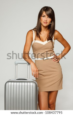 Young businesswoman in elegant beige dress going to business trip standing leaning on her silver travel suitcase, against gray background