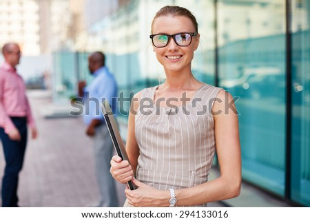 Young businesswoman in eyeglasses holding touchpad  - stock photo