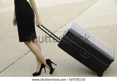 Young businesswoman in high heels and black dress drags a black suitcase across tarmac at airport
