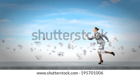 Young businesswoman in suit running in a hurry - stock photo