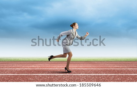 Young businesswoman in suit running on track - stock photo