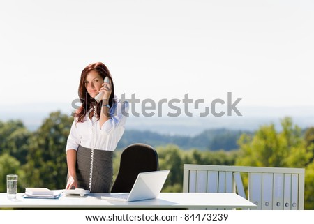 Young businesswoman in sunny nature office calling standing behind table - stock photo