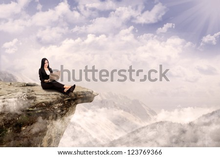Young businesswoman is relaxing while working with her laptop on a mountain - stock photo