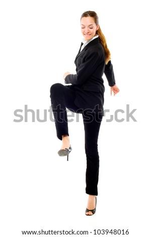 young businesswoman kicking on white background studio - stock photo