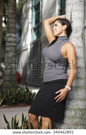 Young businesswoman leaning on a tree - stock photo