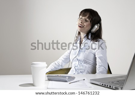 Young businesswoman listening to headphones with eyes closed at desk - stock photo