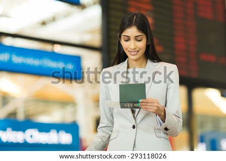 young businesswoman looking at boarding pass in front of flight information board at airport