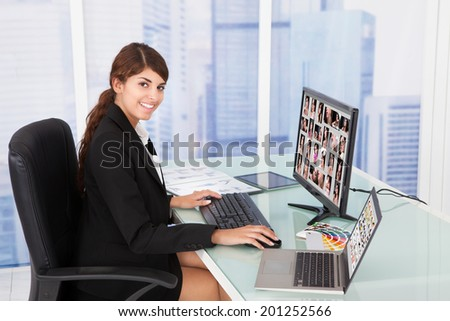 Young businesswoman looking at color swatches at computer desk in office - stock photo