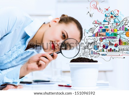 Young businesswoman looking at drawn image of sprout through magnifier - stock photo
