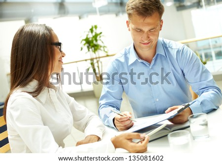 Young businesswoman looking at her business partner explaining document - stock photo