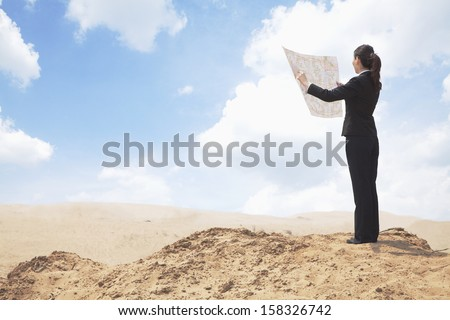 Young Businesswoman looking at map in the middle of the desert - stock photo