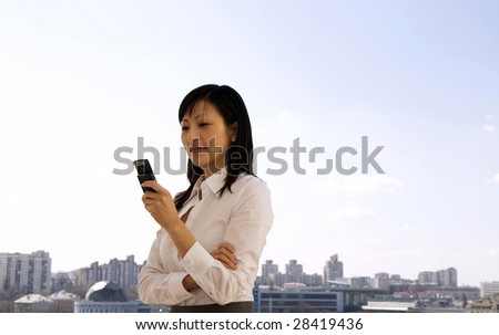young businesswoman looking on the mobile phone, outside