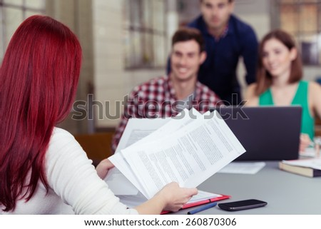 Young businesswoman looking through paperwork as she sits with her back to the camera in a meeting with her co-workers, focus to her and the documents - stock photo