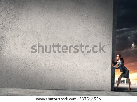 Young businesswoman making effort to move cement wall - stock photo