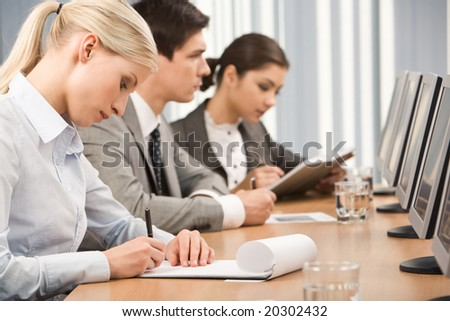 Young businesswoman making notes in her notepad in working environment - stock photo
