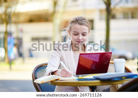 Young businesswoman on a coffee break, using her mobile laptop - stock photo