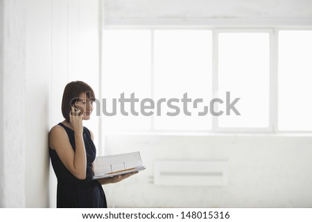 Young businesswoman on call while holding file in empty warehouse - stock photo
