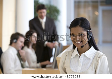 Young businesswoman on headset with seated working colleagues behind