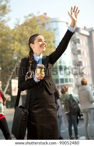 young businesswoman on street waving hello, business people - stock photo