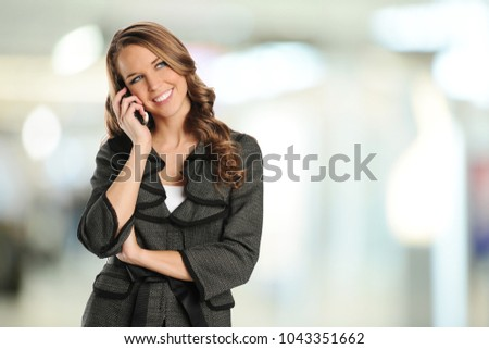 Young businesswoman on the cell phone inside an office building