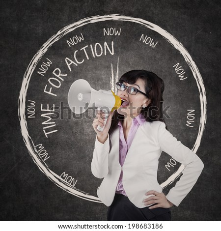 Young businesswoman or teacher announcing an order using megaphone in classroom - stock photo
