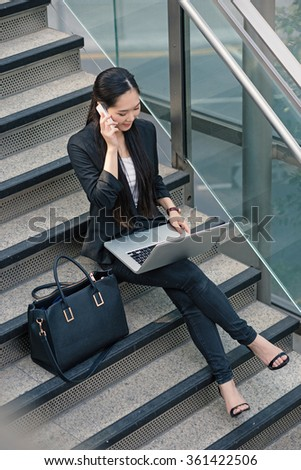 Young businesswoman portrait working with laptop and talking at the phone sit on stairs. - stock photo