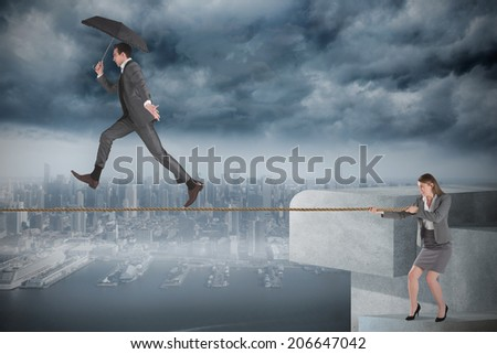 Young businesswoman pulling a tightrope for businessman against coastline and city - stock photo