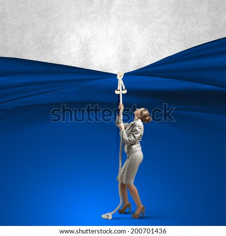 Young businesswoman pulling curtain with rope. Place for text - stock photo