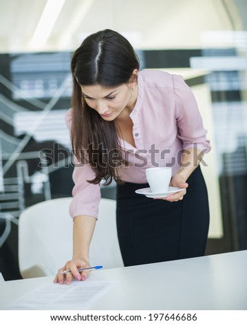 Young businesswoman reading document while holding coffee in office - stock photo