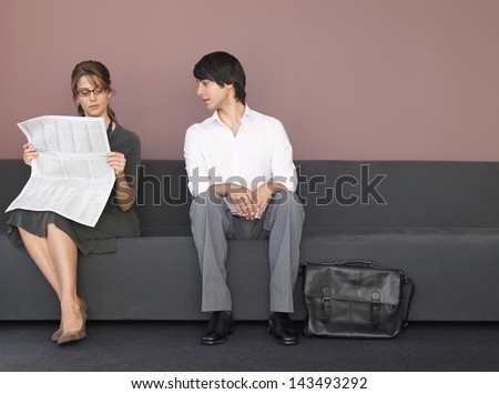 Young businesswoman reading newspaper sitting beside male colleague on sofa - stock photo