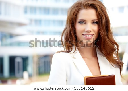 Young businesswoman (real estate agent) presenting detached modern office - stock photo