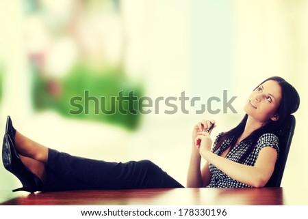 Young businesswoman relaxing at the desk, legs up - stock photo