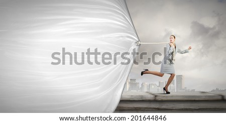 Young businesswoman running and pulling white blank banner - stock photo