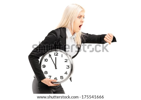 Young businesswoman running late with a wall clock in her hand isolated on white background - stock photo